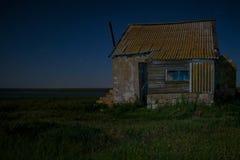 Nattlandskap med det övergav spöklika huset Arkivfoton