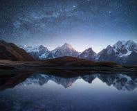 Nattlandskap med en bergsjö och en stjärnklar himmel arkivfoton