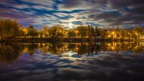 Nattlandskap ovanför floden med träd som tänds av stadsljus och moln i rörelse royaltyfria bilder