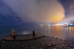 Nattlandskapet till staden tänder i moln nära Royaltyfri Foto