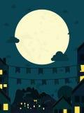 Nattliten stad med den stora moonen Arkivfoto