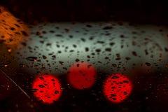 Nattljus av stads- trafik som ses till och med vindrutan i regnigt väder abstrakt bakgrund Begrepp av nattstaden Royaltyfri Foto