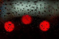 Nattljus av stads- trafik som ses till och med vindrutan i regnigt väder abstrakt bakgrund Begrepp av nattstaden Royaltyfria Bilder