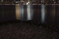 Nattljus reflekterade i vattnet, stenar på kusten Royaltyfri Bild