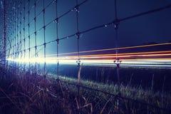 Nattmotorväg med härligt hastighetslogistiktema av ljusa strimmor till och med staketet Trucker Industry för gammalt land fotografering för bildbyråer