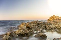 Nattnedgångar över den steniga seacosten Fotografering för Bildbyråer