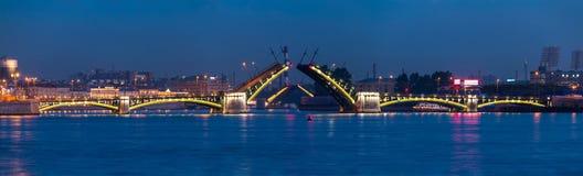 Nattpanorama av den öppna Birzhevoy bron och den Tuchkov bron arkivfoto