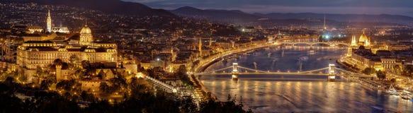 Nattpanorama av den Budapest staden - huvudstad av Ungern Parlamentbyggnad på rätt, Buda slottkulle på den vänstra och Chain bron Royaltyfri Foto
