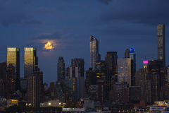 Nattplats: Toppna fullmåne- och stadsljus Royaltyfria Bilder