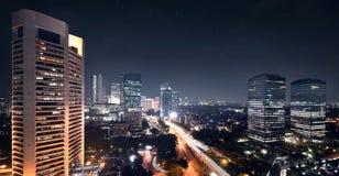 Nattplatsen med ljusa skyskrapor och trafik vinkar Royaltyfria Foton