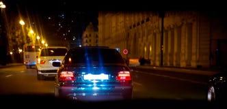Nattsikt av bilarna vägen i staden på natten med gult och rött elektriskt ljus för bilar under är de kommande hom arkivfoton