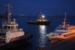 Nattsikt av bogserbåten i lastporten av Odessa Bogserbåtar och en sväva kran är i port Nattpanorama av porten royaltyfri bild