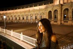 Nattsikt av den härliga unga kvinnan i Plaza de Espana, Seville, Spanien royaltyfri bild