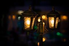 Nattsikt av den orange ljusa lamplyktan för tappning två med garnering Selektiv fokus med mjuk bokeh royaltyfri foto