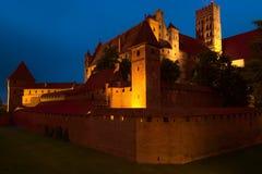 Nattsikt av den Teutonic beställningsslotten i Malbork, Polen Royaltyfria Bilder