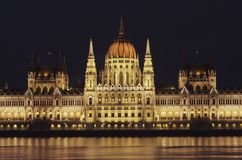 Nattsikt av den upplysta byggnaden av den ungerska parlamentet i Budapest A den härliga reflexionen av parlamentet arkivfoton