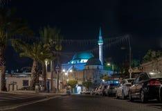 Nattsikt av den Weizman gatan och al-Jazzarmoskén i den gamla staden av Akko i Israel arkivbild