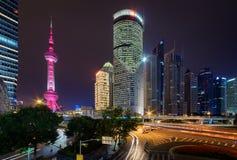 Nattsikt av det orientaliska pärlemorfärg tornet och andra skyskrapor Arkivbilder