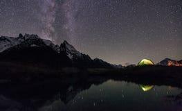 Nattsikt av det upplysta tältet nära sjön arkivbilder