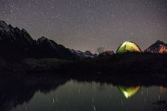 Nattsikt av det upplysta tältet nära sjön arkivfoto