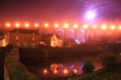 Nattsikt av Dinan på den Rance floden Royaltyfri Bild