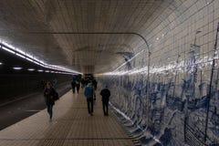 nattsikt av en gångtunnel med övergående och blåa målningar för folk på tegelplattaväggen royaltyfri foto