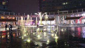 Nattsikt av färgrika vattenlekar av springbrunnarna i den Gael Aulenti fyrkanten i Milan den sista dagen stock video