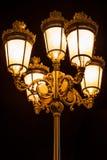 Nattsikt av fem härliga dekorativa bronsgataljus tillsammans på en lampost utomhus arkivfoto