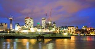 Nattsikt av flodThemsen i London med HMS Belfast mot en upplyst bakgrund arkivfoton
