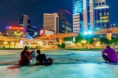 Nattsikt av Silom det finansiella området med folk Royaltyfria Foton
