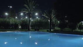 Nattsikt av simbassängen på semesterort arkivfilmer