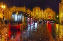Nattsikt av staden med spårvagnen och röda ljus Effekt för rörelsesuddighet Arkivfoto