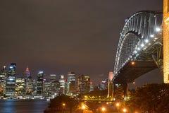 Nattsikt av Sydney Harbour Bridge & området för central affär Arkivfoto
