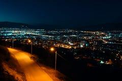 Nattsikt från över huvudstad av Georgia, Tbilisi Gataljus och kullar som omger staden blå sky - Bild royaltyfri fotografi