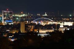 Nattsikt på staden Röda ljus, byggnader, bro och fabrik arkivfoto