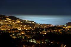 Nattsikt till Nice med månsken på vattnet Fotografering för Bildbyråer