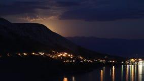 Nattsikt under måneljuset på staden på en kust av Adriatiskt havet från den steniga kullen i Kroatien, olika färgsignaler arkivbilder