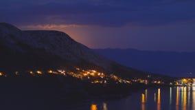 Nattsikt under måneljuset på staden på en kust av Adriatiskt havet från den steniga kullen i Kroatien, olika färgsignaler arkivbild