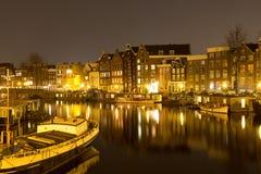 Nattsikten av byggnader i Amsterdam reflekterade i en kanal, Holl fotografering för bildbyråer