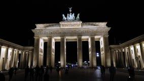 Nattsikten av den Brandenburg porten i Berlin, folk går i fyrkanten, Tyskland på natten, Berlin stock video