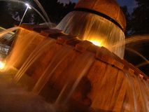 Nattsikten av den Herzel lokalen parkerar flödande vatten för grodaspringbrunnen, exponerat av varma gula ljus royaltyfri bild
