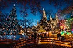 Nattskott av julmarknader på Rathausplatz, tänt utsmyckat träd med färgrika ljus, stadshus i bakgrunden fotografering för bildbyråer