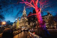 Nattskott av julmarknader på Rathausplatz, tänt utsmyckat träd, stadshus i bakgrunden royaltyfri fotografi