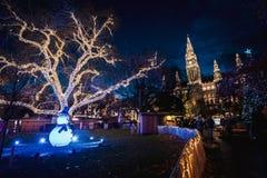 Nattskott av julmarknader på Rathausplatz, tänt utsmyckat träd, stadshus i bakgrunden arkivfoton