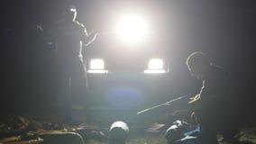Nattskottet av två mans att resa upp tältet i ligh från expeditions- SUV lager videofilmer