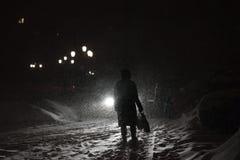 Nattsnöfall och en man i ljuset av en lykta royaltyfri foto