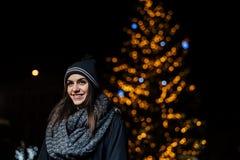 Nattståenden av en härlig brunettkvinna som ler tycka om vinter parkerar in Vinterglädje vinter för snow för pojkeferielay positi royaltyfri fotografi