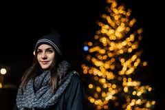 Nattståenden av en härlig brunettkvinna som ler tycka om vinter parkerar in Vinterglädje vinter för snow för pojkeferielay positi arkivfoto
