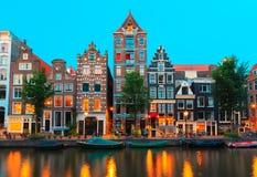 Nattstadssikt av Amsterdam kanaler och typisk ho Arkivfoton