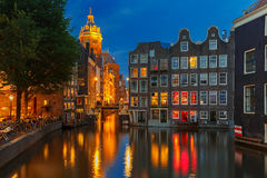 Nattstadssikt av den Amsterdam kanalen, kyrkan och brien arkivfoto